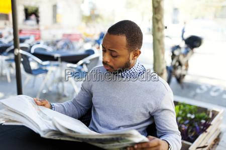 young man reading newspaper at street