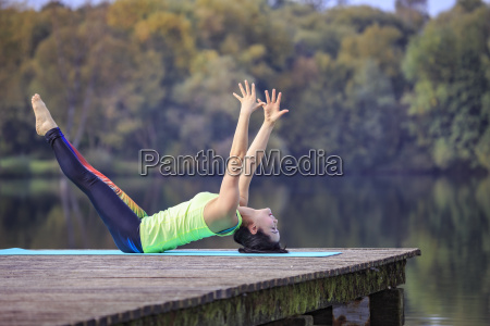 woman practicing yoga on jetty at