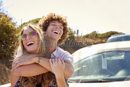 carefree couple hugging outdoors in summer