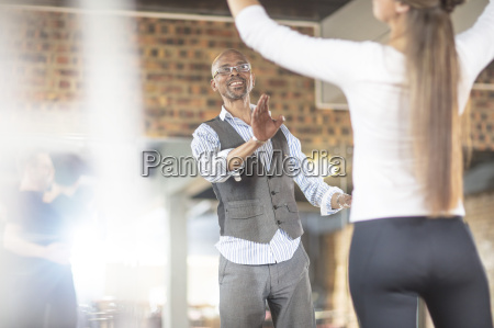 instructor teaching female dancer in studio