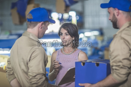 woman with clipboard talking to workers