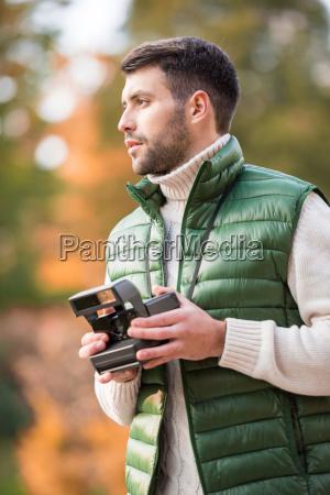 handsome man holding instant camera