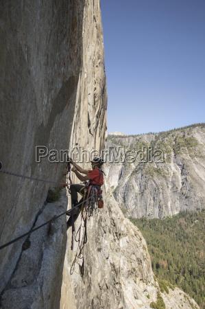 man climbing on rocky mountain of