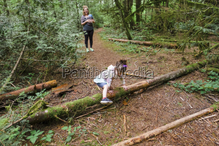young girl climbs over a log