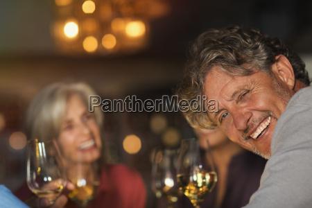 portrait laughing senior man drinking white