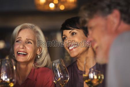 smiling women drinking white wine at