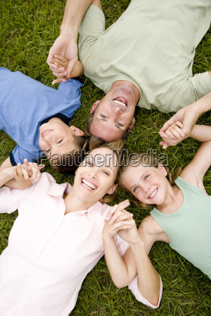 family lying on ground holding hands