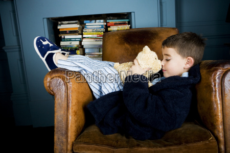 little boy lying in armchair with