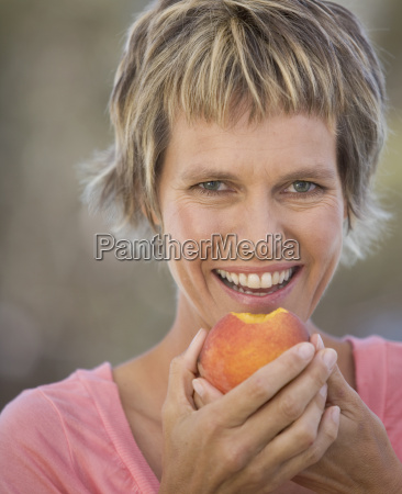 a woman eating a peach