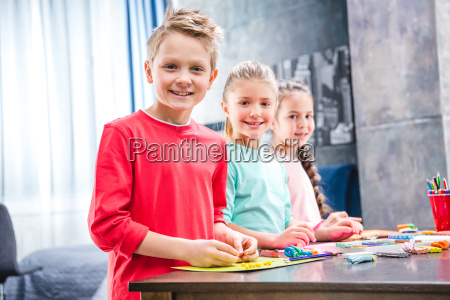 schoolchildren playing with plasticine