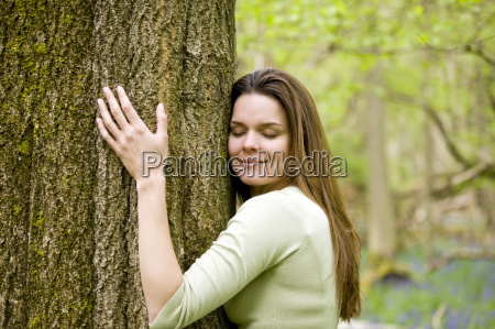 a young woman in woodland hugging