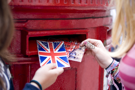 two teenage girls putting postcards into