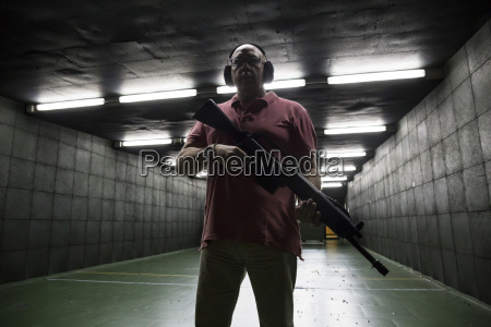 man holding a tactical weapon in