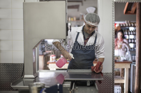 butcher cleaning work surface in butchery