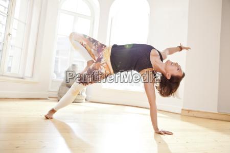 woman in sunny yoga studio moving