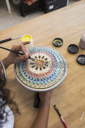 woman painting a ceramic plate with