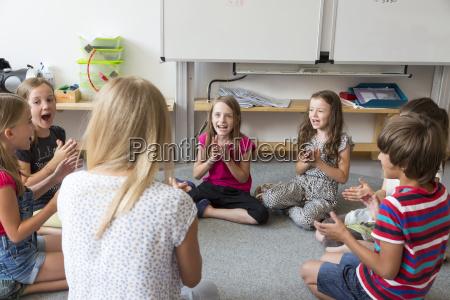 teacher and pupils sitting on floor