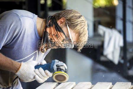 man sanding wood with a random