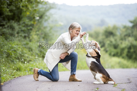 senior woman teaching her dog