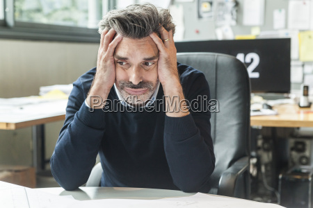 mature man sitting in office with