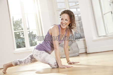 happy woman getting into yoga pose
