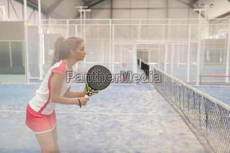 concentrated female paddle tennis player on