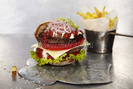 juicy cheeseburger with french fries in