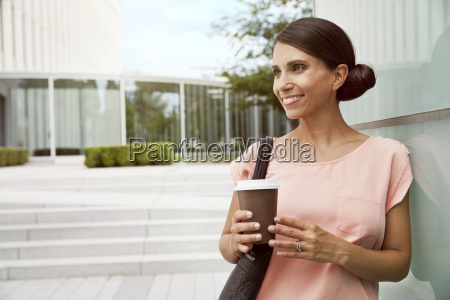 smiling woman holding takeaway coffee outdoors