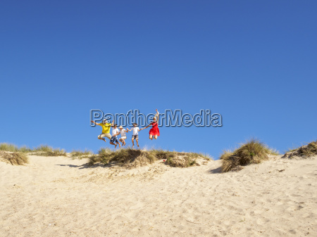 family jumping from sand dune