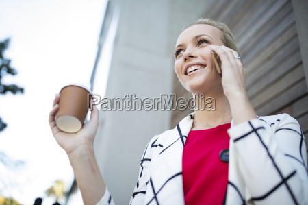 smiling woman with takeaway coffee talking