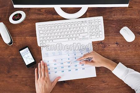 businessman marking date on calendar