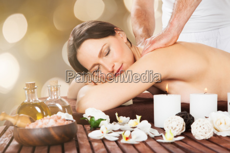 relaxed woman receiving shoulder massage