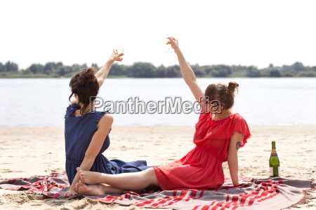 two friends sitting on the beach
