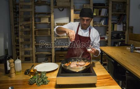 man pouring salt on beef cheeks