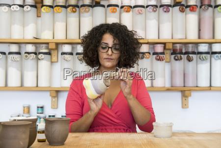 woman painting a ceramic mug with