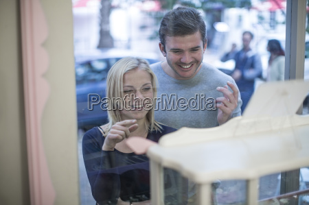 smiling young couple looking in shop