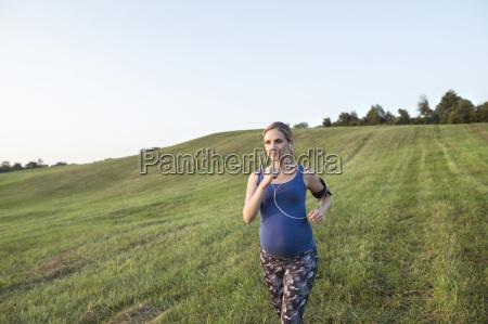 pregnant woman jogging in field