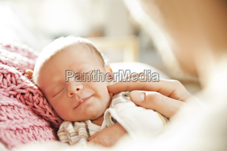 sleeping newborn baby being touched by