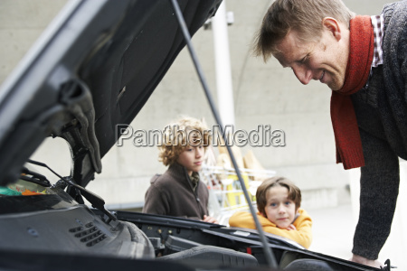 father looking at broken car while