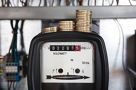 stacked coin on kilowatt meter