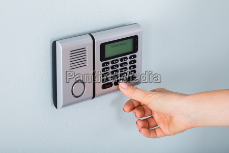 person hand using home security alarm
