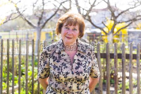 happy elderly woman is standing proud