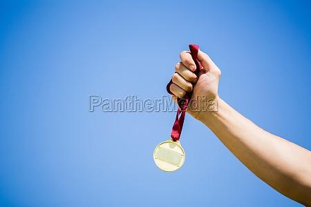athlete hand holding gold medal after