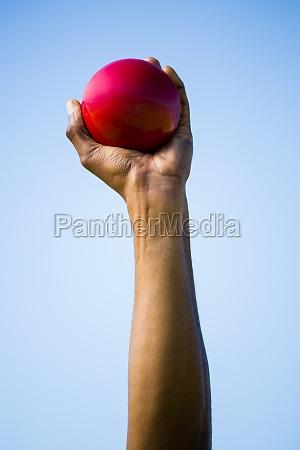 athletes hand holding shot put ball