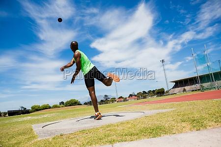 male athlete throwing shot put ball
