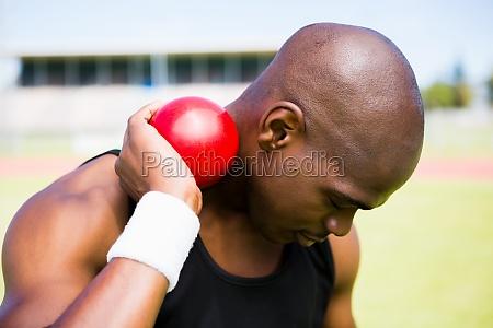 male athlete holding shot put ball