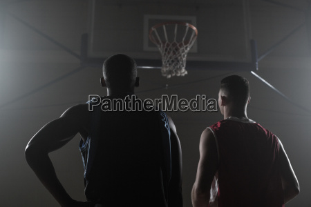 two basketball player looking the basketball