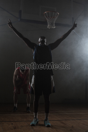 victorious basketball player raising his arms
