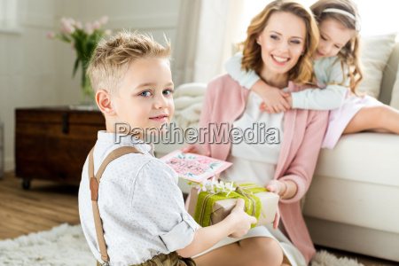 boy presenting gift to mother