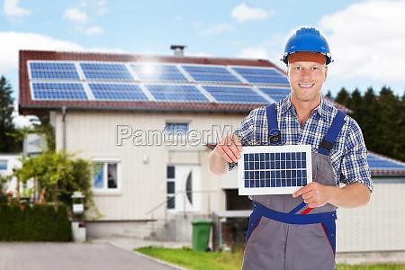 smiling repairman holding solar panel